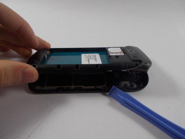 گوشی Galaxy S Blaze تعمیری را مثل عکس اول روی میز کارتان قرار دهید. نوک قاب باز کن را از لبه سمت راست قاب به شکاف مابین بدنه گوشی و فریم میانی آن فرو ببرید و خیلی آرام سعی کنید فریم میانی را به سمت بالا هدایت نمایید تا از روی بدنه گوشی بلند شود.