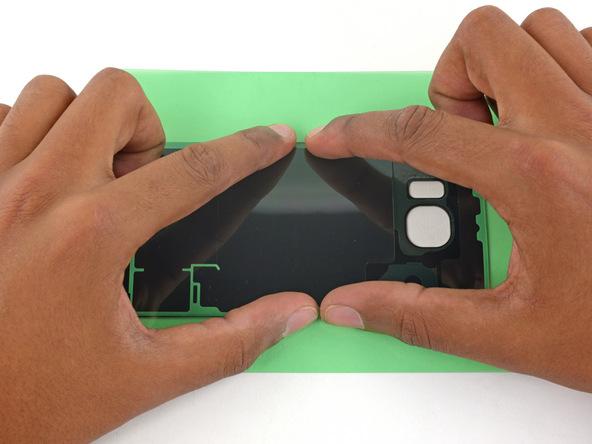با انگشت خود لاستیک آب بندی را روی درب پشت گوشی فشار دهید تا بخش زیرین آن کاملا روی درب پشت گوشی محکم شود.
