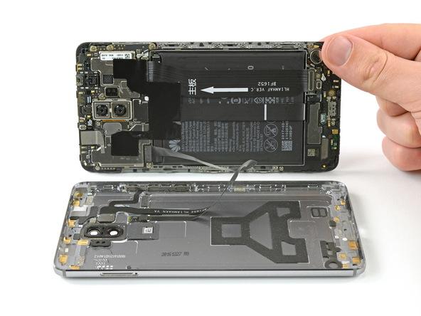 میت 9 تعمیری را به شکلی روی میز کارتان قرار دهید که LCD آن روی به سمت بالا قرار گیرد. نوک قاب باز کن پلاستیکی را وارد لبه سمت چپ قاب آن کنید و با آن درب پشت گوشی را روی میز کارتان فشار داده و نگه دارید.