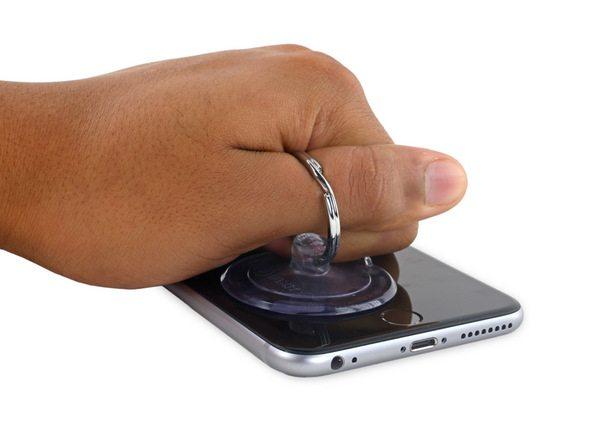 آیفون 6 اس پلاس تعمیری را روی میز کارتان قرار دهید. دست خود را روی آیفون قرار داده و با انگشت گیره ساکشن کاپ را بگیرید. مادامی که کف دستتان روی نمایشگر گوشی تکیه داده و از جابجا شدن آن جلوگیری میکند، با انگشت ساکشن کاپ را به سمت بالا بکشید و به تدریج نیروی کششی را تا جایی افزایش دهید که در لبه زیرین قاب آیفون 6 اس پلاس تعمیری یک شکاف کوچک ایجاد شود.