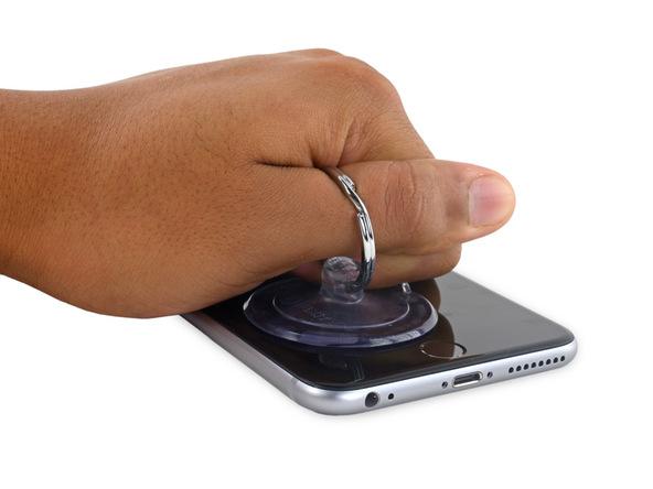 آیفون 6 اس پلاس تعمیری را روی میز کار قرار دهید. دستتان را مشت کرده و مثل عکس به گونهای روی نمایشگر گوشی قرار دهید که انگشت شصتتان در گیره ساکشن کاپ قرار بگیرد و بتوانید از آن برای کشیدن ساکشن کاپ استفاده کنید. به آرامی ساکشن کاپ را با تمرکز نیرو روی لبه زیرین آیفون به سمت بالا بکشید و به تدریج شدت نیروی کششی اعمالی را افزایش دهید. شدت نیروی کششی را تا جایی افزایش دهید که در لبه زیرین قاب آیفون 6S Plus تعمیری یک شکاف باریک (مثل عکس دوم) ایجاد شود.