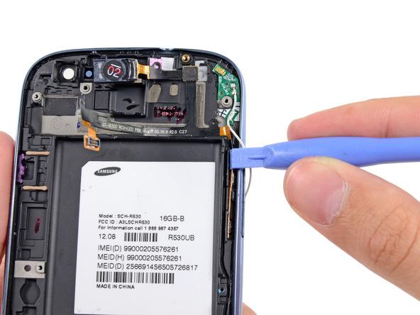 نوک قاب باز کن یا اسپاتول را در لبه سمت راست قاب گوشی (از نمایش پشت) قرار داده و در شیار موجود حرکت دهید تا سیم دکمه ولوم آزاد شود.