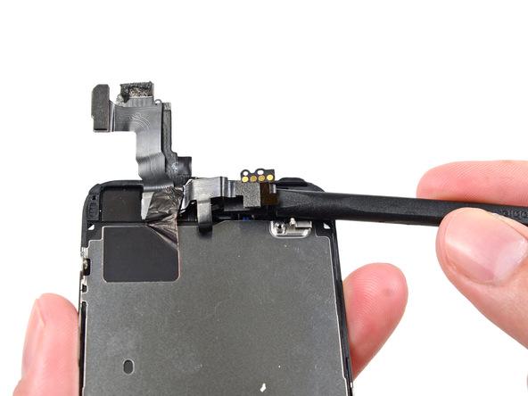 نوک اسپاتول را زیر سیم دوربین جلو آیفون 5S قرار داده و خیلی آرام این قطعه و کل سیم مجموعه دوربین گوشی را به سمت بالا بکشید تا به محل چسبانده شدن سیم روی پلیت محافظ ال سی دی آیفون برسید.