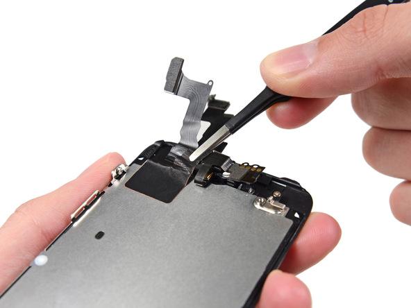 به آرامی گوشه سمت چپ و پایین سیم مجموعه دوربین (مخل چسبیدن سیم به پلیت محافظ ال سی دی) را با پنس گرفته و به سمت بالا بکشید تا چسب روی پلیت ال سی دی باز شود.