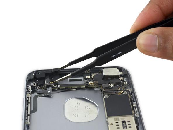 با نوک پنس فلت آنتن وای فای آیفون 6 اس پلاس تعمیری را گرفته و آن را از مسیر کابل کنترل صدای گوشی خارج کنید. بدین منظور فلت آنتن وای فای را به سمت لبه فوقانی قاب پشت گوشی هدایت نمایید.