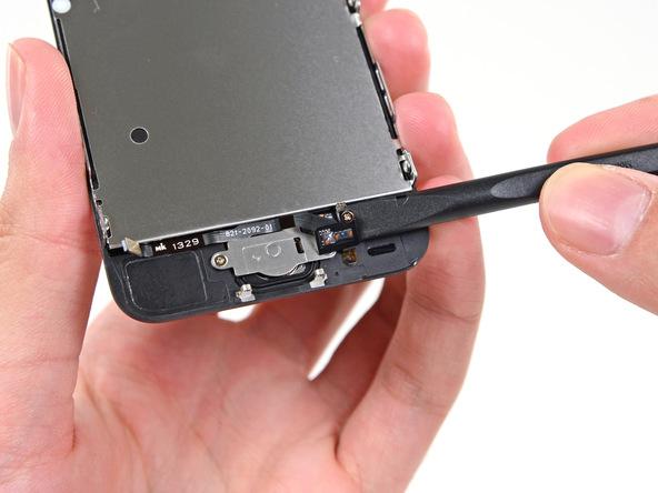 نوک اسپاتول را زیر سیم دکمه هوم آیفون 5S تعمیری قرار داده و خیلی آرام آن را به سمت پایین هول دهید تا از روی براکت دکمه هوم کنار زده شود.