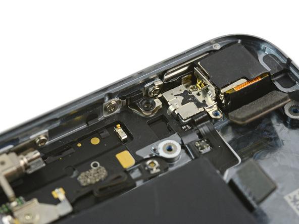 در بخش فوقانی پنل پشت آیفون SE و نزدیک دوربین اصلی آن یک مجرای پیچ قرار دارد که در عکس های ضمیمه شده آن را میبینید. در زیر این مجرا یک پلیت فلزی قرار گرفته که ممکن است در اثر جابجا کردن و تکان دادن پنل پشت آیفون SE از جایگاهش خارج شده و گم شود. بنابراین آن را با نوک پنس از زیر مجرای پیچ مذکور خارج کنید.