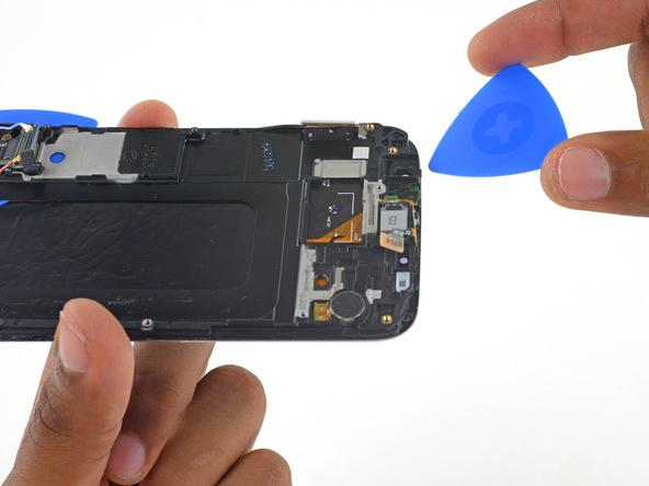 یک پیک را به آرامی به زیر لبه فوقانی قالب پلاستیکی روی نمایشگر گوشی فرو کنید.