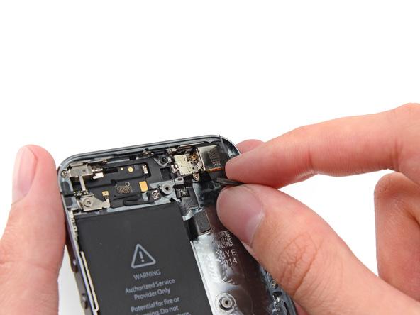 لنز دوربین اصلی آیفون 5s تعمیری را از گوشه درب پشت جدا کنید.