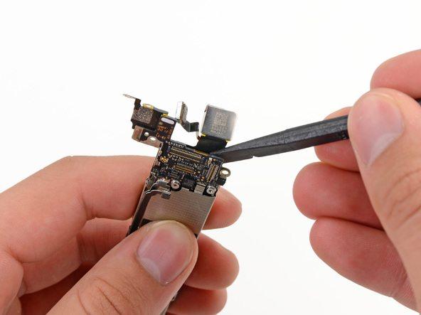 با نوک اسپاتول کابل لنز دوربین اصلی آیفون 5 را از روی مادربرد گوشی جدا کنید.