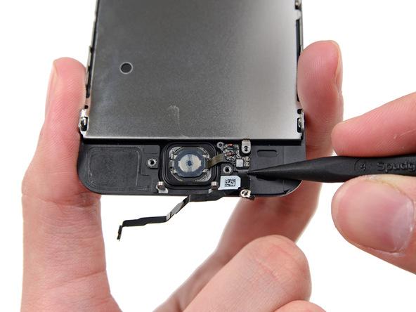 نوک اسپاتول را به آرامی در زیر سیم دکمه هوم آیفون 5S تعمیری فرو برده و آن را از روی درب پشت گوشی جدا کنید.