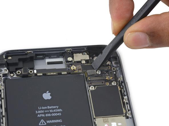 نوک پهن اسپاتول را در گوشه سمت راست کانکتور دکمه پاور آیفون 6 اس پلاس تعمیری قرار داده و آن را از روی برد جدا کنید.
