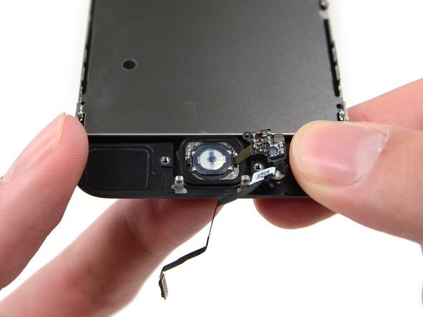 انگشت خود را زیر دکمه هوم آیفون 5S تعمیری قرار داده و خیلی آرام به گونهای آن را به سمت داخل هول دهید که لبه فوقانی دکمه هوم از جایگاهش بلند شود.