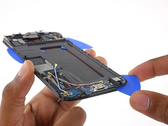 یک پیک را به آرامی در گوشه سمت راست لبه زیرین فریم پلاستیکی روی نمایشگر فرو ببرید. دقت کنید که برد ثانویه گوشی دقیقا در این بخش قرار دارد، بنابراین پیک باید در گوشه برد ثانویه فرو برده شود.
