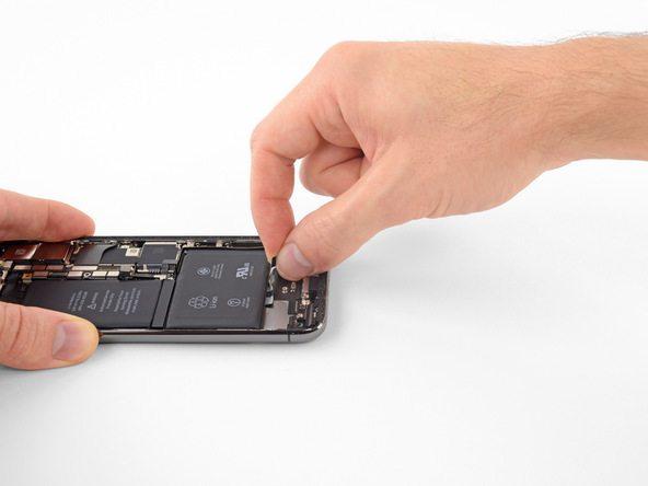 لبه چسب گوشه مخالف همان قسمت باتری را گرفته و مثل حالت قبل با نیروی یکنواخت به سمت عقب بکشید (چسب وسط را در حالت خودش رها کنید). کشیدن با نیروی یکنواخت را تا جایی ادامه دهید که چسب از زیر باتری گوشی آزاد شود.