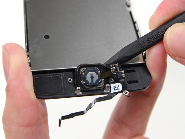 نوک اسپاتول را از لبه فوقانی دکمه هوم به زیر آن فرو برده و خیلی آرام این دکمه را به سمت پایین هدایت کنید تا لبه های سمت راست و چپ دکمه هم آزاد شوند.