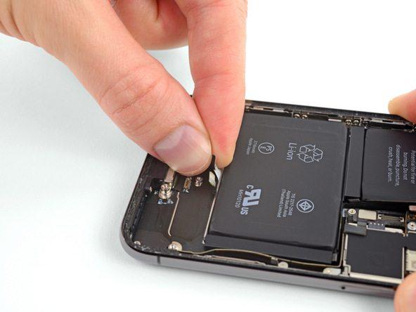 یکی از چهار چسب نگهدارنده باتری در رو به روی سه چسب دیگر نصب است. لبه این چسب را گرفته و مثل چسب های قبل یا نیروی یکنواخت به سمت عقب بکشید تا کاملا از زیر باتری جدا شود.