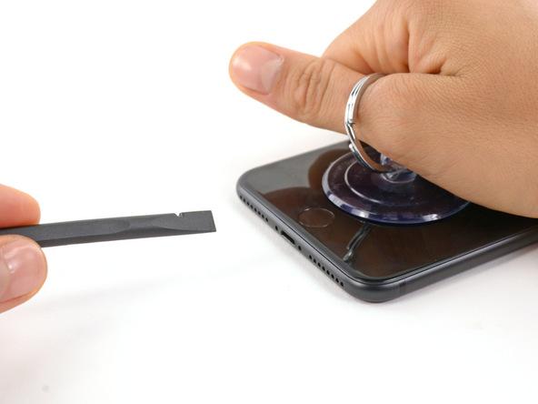 آیفون 7 پلاس تعمیری را روی میز کار قرار دهید و ساکشن کاپ را با تمرکز نیرو روی لبه زیرین به سمت بالا بکشید. با توجه به اینکه قبلا به لبه زیرین گوشی گرما داده بودید و لاستیک آب بندی این بخش را ضعیف کرده بودید، شکاف بسیار ریزی در بین پنل رو و پشت گوشی در لبه زیرین ایجاد میشود. به محض مشاهده این شکاف نوک اسپاتول را به درون آن فرو کنید.