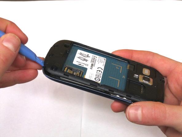 نوک قاب باز کن پلاستیکی را به آرامی از لبه زیرین قاب گوشی به زیر فریم میانی روی مادربرد فرو ببرید و سعی کنید آن را از روی بدنه Galaxy S3 Mini (گلکسی اس 3 مینی) تعمیری بلند نمایید.