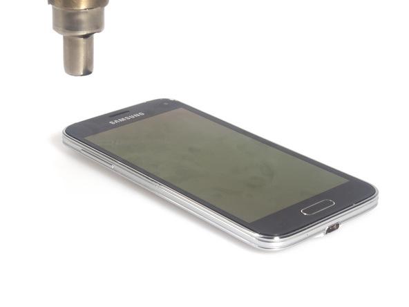 با سشوار یا آیاوپنر (iOpener) برای مدت زمان 1 دقیقه به لبه های قاب گلکسی اس 5 مینی تعمیری گرمای ملایمی وارد کنید.