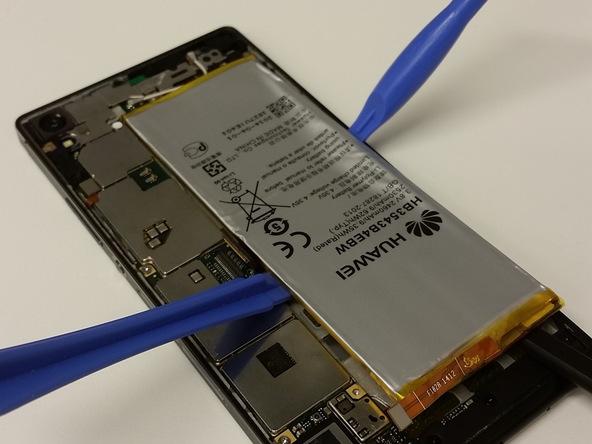برای جداسازی باتری باید از چند ابزار مختلف به صورت همزمان استفاده کنید. ابتدا یک پیک یا قاب باز کن پلاستیکی را از لبه سمت راست باتری به زیر آن فرو ببرید و سعی کنید باتری را از روی قاب گوشی بلند کنید.