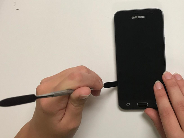 نوک قاب باز کن یا اسپاتول را در لبه قاب Galaxy J3 تعمیری فرو ببرید و بدنه اصلی این گوشی را از بخش جلوی آن جدا کنید.