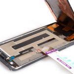 به آرامی با نوک قاب باز کن لبه زیرین ال سی دی گلکسی نوت 4 تعمیری را از روی بدنه گوشی بلند کنید. لبه زیرین ال سی دی را با دست گرفته و به شکل کتابی از روی بدنه دستگاه بلند نمایید تا زاویهای در حدود 60 الی 70 درجه پیدا کند.