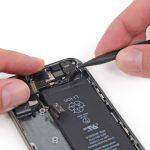با حرکت دادن اسپاتول در لبه زیرین باتری آیفون 5s، گوشه چسب نگهدارنده باتری موجود در این قسمت را باز کنید.