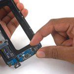 با انگشت خود بخش میانی سوکت شارژ با همان برد ثانویه گلکسی اس 6 تعمیری را گرفته و بخش زیرین آن را به سمت بالا هول دهید. سپس آن را به سمت عقب بکشید تا کامل از روی فریم پلاستیکی روی نمایشگر جدا شود.