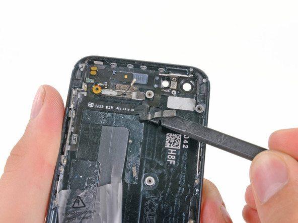 نوک اسپاتول را زیر سمت راست سیم دکمه پاور و ولوم آیفون 5 تعمیری قرار داده و آن را از روی درب پشت گوشی باز کنید.