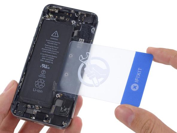 یک قاب باز کن کارتی را زیر باتری آیفون 5S فرو برده و سعی کنید آن را از روی درب پشت گوشی بلند نمایید.