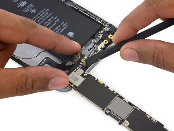 نوک پهن اسپاتول را در گوشه کابل آنتن بلوتوث آیفون 6 اس پلاس تعمیری قرار داده و خیلی آرام آن را از روی برد گوشی جدا نمایید.