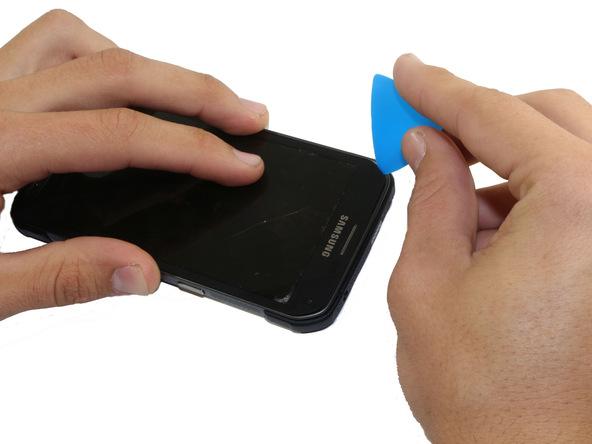 گلکسی اس 5 اکتیو را روی میز کارتان قرار دهید. با یک دست بدنه گوشی را نگه دارید و با دست دیگرتان سعی کنید نوک یک پیک را در گوشه سمت چپ و بالای قاب گلکسی اس 5 اکتیو فرو ببرید. برای انجام این کار باید با پیک بازی کنید تا کاملا به زیر ال سی دی گوشی فرو برود.