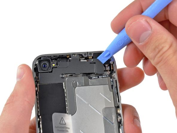 نوک قاب باز کن پلاستیکی را به آرامی از گوشه سمت راست به زیر آنتن وای فای آیفون 4 تعمیری که شبیه به یک درپوش است فرو برده و این قطعه را به سمت بالا هول دهید تا از روی برد گوشی بلند شود.