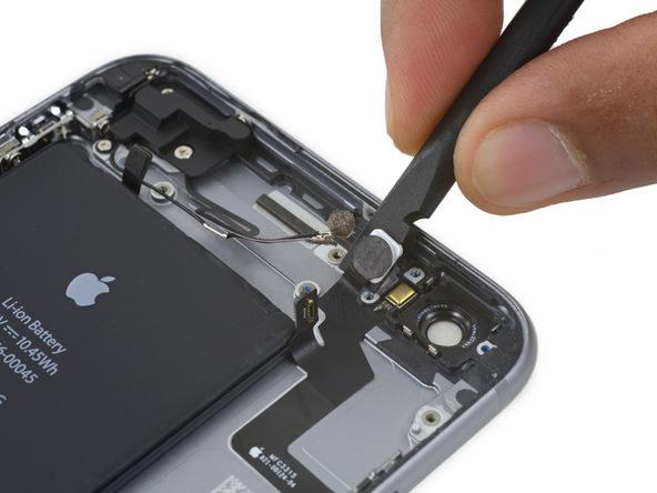 نوک اسپاتول را به آرامی از کنار چراغ فلش دوربین اصلی آیفون 6 اس پلاس به زیر کابل دکمه پاور فرو برده و آن را کمی به سمت جلو هول دهید تا کابل مذکور تا لبه باتری گوشی از روی پنل پشت جدا شود.