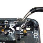 با نوک اسپاتول دکمه پاور آیفون 5S تعمیری را به سمت داخل هول دهید و سپس آن را به راحتی از درب پشت گوشی جدا نمایید.
