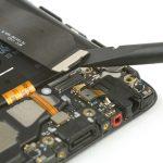 کانکتور کبل اینترکانکت (اتصال دهنده برد سوکت شارژ به برد اصلی گوشی) را با نوک اسپاتول سر صاف از روی سوکتش آزاد کنید.