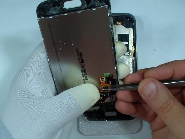 اگر قرار است فقط شیشه روی صفحه نمایش گلکسی جی 1 تعویض شود، در همین مرحله تاچ و ال سی دی گوشی را از شیشه روی آن جدا کنید. بدین منظور باید کانکتور پشت تاچ ال سی دی سامسونگ Galaxy J1 را آزاد نمایید.
