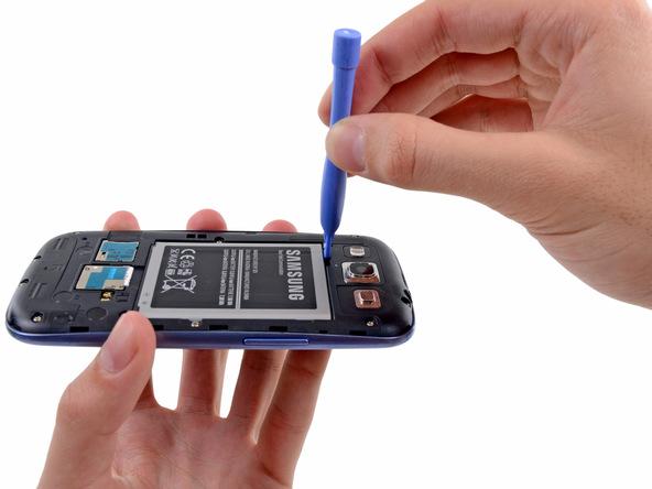 نوک قاب باز کن را به زیر لبه فوقانی باتری Galaxy S3 تعمیری فرو برده و خیلی آرام آن را از روی بدنه گوشی بلند کنید.
