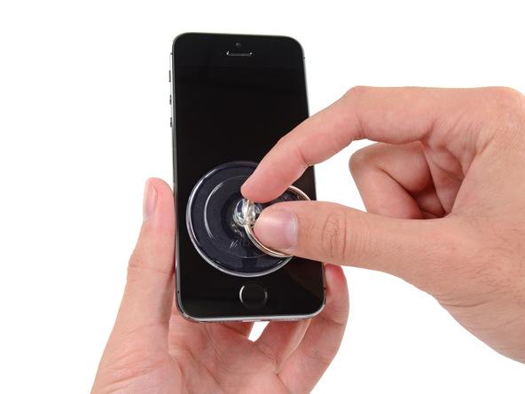 اگر ابزار iSclack (آیاسکلک) را برای باز کردن نمایشگر آیفون SE از پنل پشت در اختیار ندارید باید به روش سنتی این کار را انجام دهید. بنابراین یک ساکشن کاپ را بر روی صفحه نمایش آیفون SE نصب کنید. محل نصب ساکشن کاپ باید نزدیک به دکمه هوم و وسط عرض گوشی باشد.