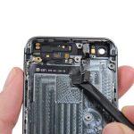 نوک اسپاتول یا یک پیک را از کنار کانکتور دکمه پاور و ولوم آیفون 5s به زیر سیم آن فرو ببرید و خیلی آرامی رو به سمت چپ و در راستای عرضی قاب گوشی حرکت کنید تا بخش زیرین سیم دکمه پاور و ولوم آیفون 5s تعمیری از روی درب پشت گوشی آزاد شود.