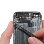 با نوک اسپاتول سمت چپ سیم دکمه پاور و ولوم آیفون 5s تعمیری را هم از روی درب پشت گوشی آزاد کنید.