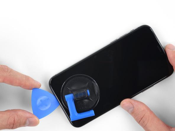پیک را به آرامی در لبه زیرین قاب آیفون X حرکت داده و به تدریج به سمت لبه چپ قاب گوشی هدایت کنید تا لاستیک های آب بندی موجود در این بخش از لبه قاب آیفون از بین بروند.
