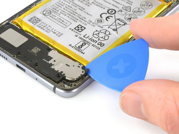 نوک پیک را از لبه سمت راست به زیر اسپیکر هوآوی P10 Lite (پی 10 لایت) فرو برده و خیلی آرام آن را به سمت بالا هول دهید تا گوشه اسپیکر از روی قاب گوشی بلند شود.