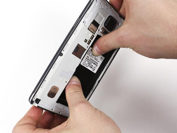 گلکسی نوت 4 تعمیری را به گونهای در دستتان بگیرید که مثل عکس اول انگشتان شست دو دستتان روی محل نشستن باتری گوشی قرار گیرد و انگشتان اشاره شما هم روی لبه های فریم میانی دستگاه واقع شوند.