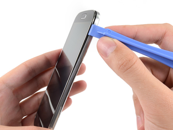 گلکسی اس 4 تعمیری را مثل عکس اول به صورت عمودی در دستتان بگیرید. نوک قاب باز کن پلاستیکی را به مابین شکاف فریم پلاستیکی روی بنه گوشی و خود بدنه آن فرو ببرید و به تدریج نوک قاب باز کن را در لبه سمت چپ قاب گلکسی اس 4 حرکت دهید تا این بخش از قاب گوشی شل شود.