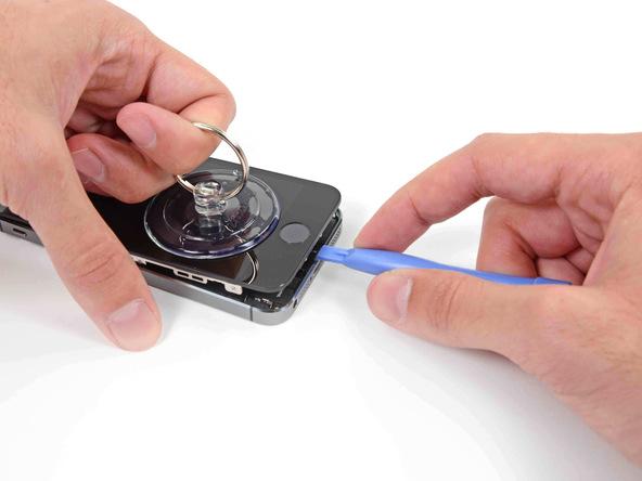 آیفون 5S تعمیری را روی میز کارتان قرار دهید و با نوک قاب باز کن لبه زیرین درب پشت آن را نگه دارید. با دست دیگرتان ساکشن کاپ را به سمت عقب و بالا بکشید و سعی کنید تمرکز نیروی کششی اعمالی روی لبه زیرین قاب آیفون معطوف باشد. به تدریج شدت نیروی کششی را افزایش دهید تا شکاف باریکی در لبه زیرین قاب گوشی ایجاد شود.