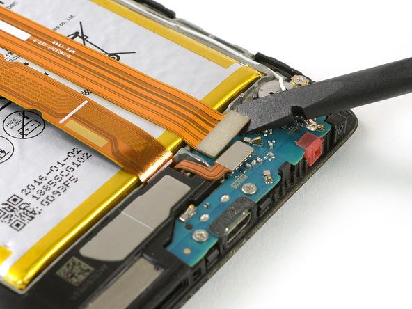 با نوک اسپاتول سر صاف کانکتور سیم اینترکانکت میت 8 را از روی فلت شارژ یا برد ثانویه گوشی آزاد کنید.