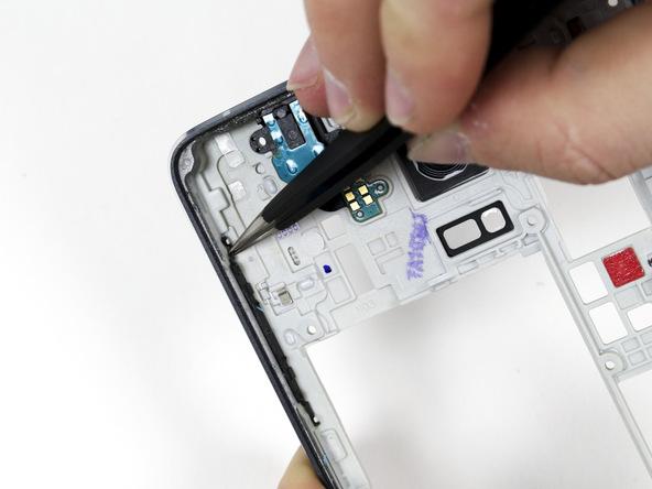 با نوک پنس گوشه فوقانی دکمه ولوم گلکسی نوت 4 تعمیری را از لبه فریم میانی گرفته و به سمت عقب بکشید. همین کار را برای گوشه زیرین دکمه هم انجام دهید تا کاملا از فریم میانی جدا شود.