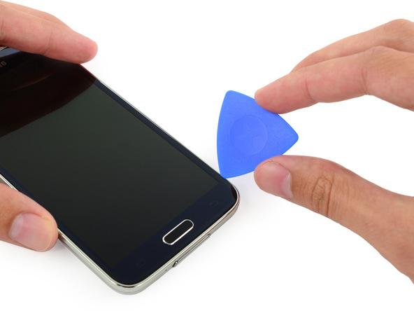 گلکسی اس 5 تعمیری را روی میز کارتان قرار دهید. با یک دست بدنه گوشی را نگه دارید و با دست دیگرتان سعی کنید لبه یک پیک را از گوشه سمت راست و پایین قاب به داخل شیار مابین نمایشگر و بدنه اصلی گوشی فرو ببرید.